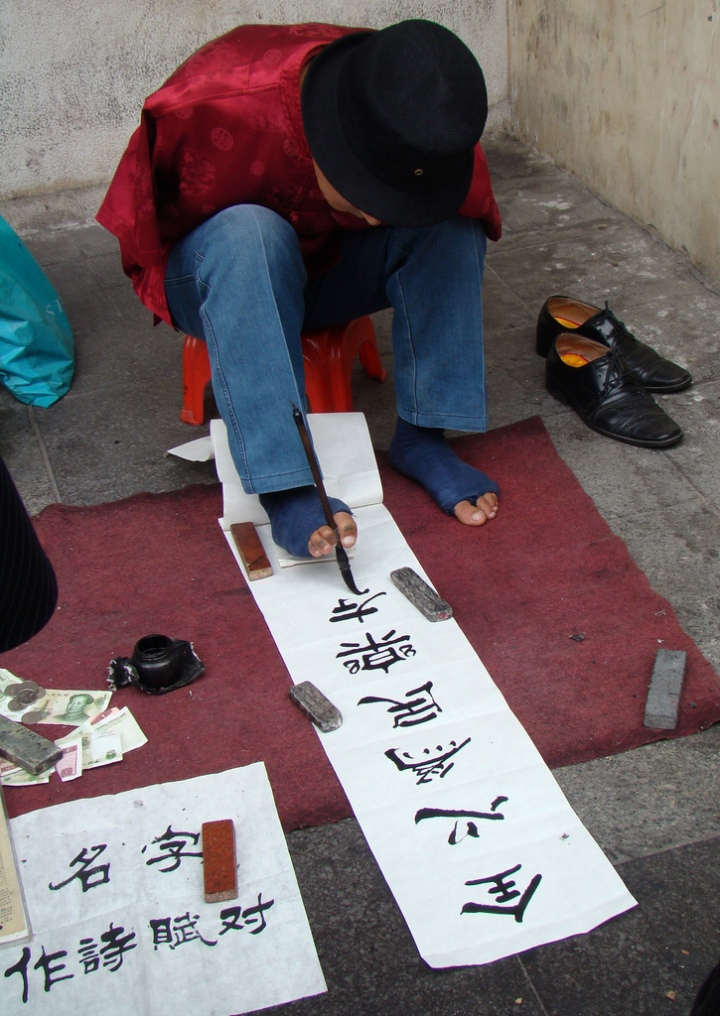 Man writing Chinese characters by holding the paint brush with his toes.
