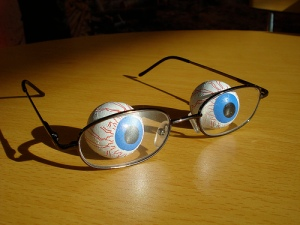 Chocolate balls in foil wrappers printed to look like eye balls (complete with blue irises and blood shot veins) behind a pair of eyeglasses sitting on a table
