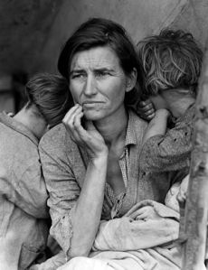 Wary looking woman sits with a baby in her arm and her chin in her hand. Two children stan on ether side of her, brying their faces in her shoulders.